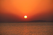 Sunset above sea. Red sun raising above ocean in early morning