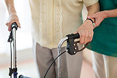 Nursing assistant helping senior woman with walking frame