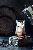 Cold refreshing iced coffee in a tall glass and coffee beans on dark background. Pouring coffee from moka pot into glass with ice cubes