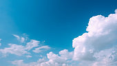 Beautiful bright blue sky with white fluffy clouds on a clear sunny day