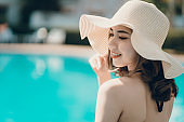 Beautiful Asain women with bikini enjoy summer vacation in the swimming pool.
