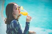Beautiful Asain women with bikini enjoy summer vacation in the swimming pool.