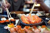 Asian lady eat a Salmon fish sashimi and Sushi in Japanese restaurant