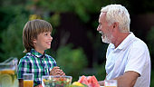 Grandfather talking to grandson, warm family relations, generation bridge