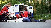 Paramedics providing emergency medical care to man on road, car accident victim