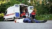 Young man lying on road, paramedics running to victim of car accident, first aid