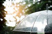 It's raining, Women walk in the rain. Hand of women holding an umbrella. She feel sad, Sky have a drizzling and overcast all the time. Raining background, Umbrella background.