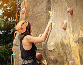 back view  sportwoman climbing up hight rock wall extreme sports  concept.