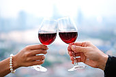 Hand of group friends celebrate successfully with red wine in the party. Young toasting in party and drinking after work hard for relax and be enjoy. Celebration Concept , Cheers!
