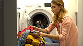 Woman putting clothes in washing machine, home laundry service, daily routine