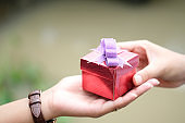 hand of man holds a red gift box to hand woman. he is preparing to give her lover.