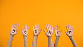 Donate written palms on orange background, volunteering project, charity event