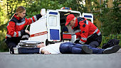 Ambulance service staff care for patient on road, putting intravenous equipment