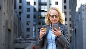 Serious head of department reading smartphone business news holding coffee cup