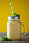 Homemade mango, lemon ice-cream or milk shake in mason jar cups, rustic wooden background. Vintage style.