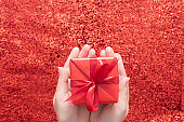 Female hands holding gift box over red glitter sparkling background, copy space. Valentine's Day.