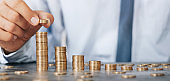Savings, stacking gold coins into increasing columns