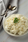 Cottage cheese isoalted on light, marble background. Dairy products, calcium and protein. Healthy breakfast. Vertical image.