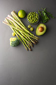 Green healthy food clean eating vegetables: asparagus, cucumber, basil, green peas, avocado, broccoli, lime, apples, grapes, broccoli on dark background, top view. Copy space.