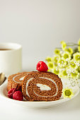 Swiss roll chocolate cake chocolate with cream. Dessert. Breakfast coffee cup and cake. Light background.