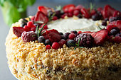 Homemade sponge cake with cream and fresh berries. Carrot and orange cake, decorated with berry. Close up sweet dessert. Whole deliciouse cake. Gray background.