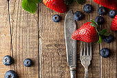 Detox, healthy food and dieting.Berriey mix, blueberry, strawberry on wood background with vintage, styled fork and knife. Styled food, fruit background. Template for social media.