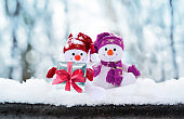 Funny two snowmen with gift box in the winter scenery. Christmas decoration