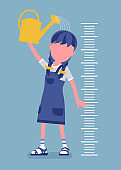 Girl at child height growth chart with a watering can
