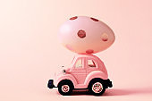 Easter egg and toy car on light pink background, happy easter day concept.