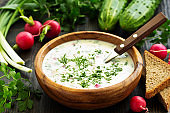 Okroshka. Summer light cold yogurt soup with cucumber, radish, eggs and dill on a wooden table. A traditional dish of Russian cuisine.