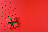 Christmas gift box on red background. Top view with copy space. Flat lay