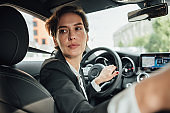 Portrait of caucasian businesswoman driving a car in reverse looking on back window