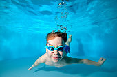 Happy smiling baby, boy, swimming underwater in swimming pool in swimming glasses and posing for camera on blue background. Portrait. Underwater photography. Vertical orientation