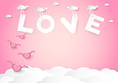 pink heart shape with wings and love word  over cloud vector background, love and valentine day concept, space for text or message design