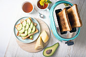 """bright, fun breakfast. cyan color toaster on a wooden background """"n"""