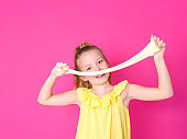 girl is playing with yellow slime in front of pink background