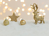 christmas items on white snow with many small, shining lights in the background