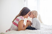 Mother and toddler son, praying at home, sitting on bed in bedroom