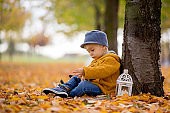 Beautiful fashion toddler boy, reading a book in park with lantern in hand and backpack