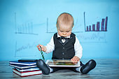 Cute toddler boy, dressed in suit and bow, talking on the phone and playing on tablet