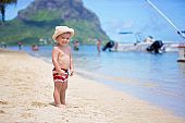 Sweet toddler boy, playing in shallow water on a tropical beach