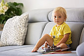 Sweet toddler boy, sitting on a couch, eating cherries and looking at picture book