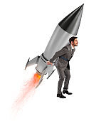 Determination and power businessman that holds a rocket isolated on white background. Increase, away