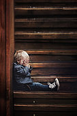 Sad child, sitting on a staircase in a big house, concept for bullying, depression