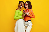 Two young beautiful hipster girls in colorful summer clothes with cocktails
