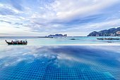 Asian tropical beach paradise in Thailand with wooden longtail boats