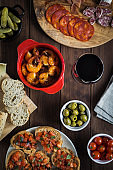 Various tapas dishes cheese and wine on a wooden table