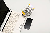Office desk, computer with smart phone and shopping cart  isolated on white background for technology and business concept.
