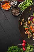 Roasting meat with vegetables, on a black wooden background. Cooking, gastronomy. Vertical frame. Delicious and healthy food, with space for an inscription.