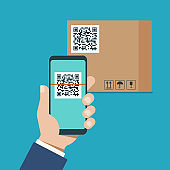 hand with a modern smartphone scans qr code on a cardboard box